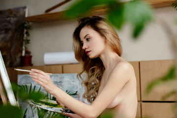 selective focus of beautiful naked young artist painting picture