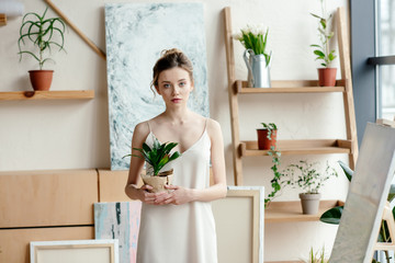 beautiful young woman holding potted plant and looking at camera in art studio
