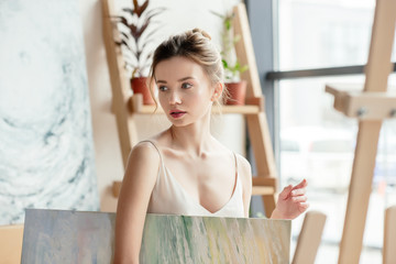 beautiful pensive girl holding picture and looking away in art studio
