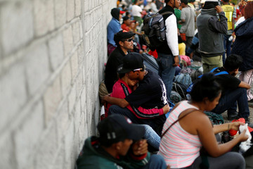 A couple of Central American migrants, moving in a caravan through Mexico, are seen next to the railway as they wait to try and board a freight train, in Irapuato