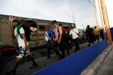 Central American migrants, moving in a caravan through Mexico, walk to the railway to try and board a freight train, in Irapuato