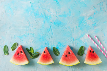 Frame of watermelon slices and mint on blue texture