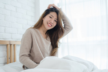 Happy beautiful young Asian woman waking up in morning, sitting on bed, stretching in cozy bedroom, looking through window. Funny asian woman after wake up. Asia woman is stretching and smiling.