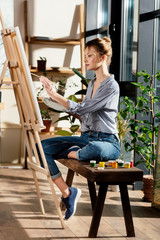 side view of female artist sitting on bench with paints and drawing picture on easel