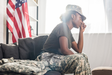 African american female soldier sitting on sofa
