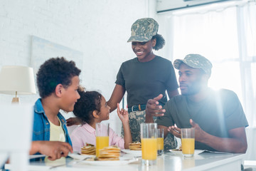 Woman and man in army uniform with their children by kitchen table