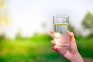 Woman hand holds a glass of cold water on outdoors background with copy space.