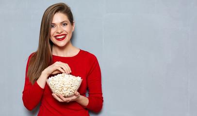 Young woman wearing red shirt eating pop corn.