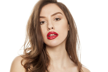 Young beautiful woman posing with red lipstick on her lips, on white background
