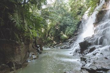 scenic view of beautiful Kanto Lampo Waterfall, green plants and rocks, Bali, Indonesia