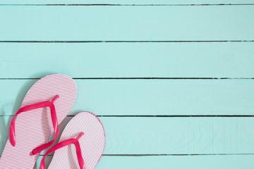 Pink flip flops on blue  wooden background