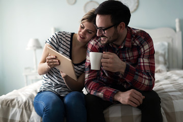 Young attractive couple using tablet in bedroom
