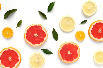 Fototapete - Pattern of fresh fruits on a white background, top view, flat lay.   Composition of green leaves and slices of citrus fruits: grapefruit, lemon, mandarin. Healthy food background, wallpaper, collage.