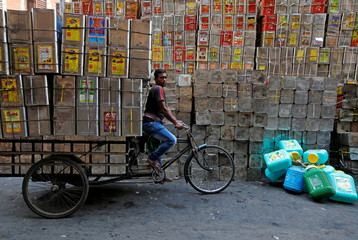 A man pedals a tricycle loaded with empty cooking oil containers in Kolkata