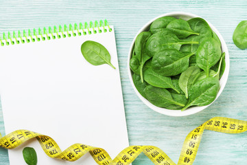 Notebook, green spinach leaves and tape measure on wooden table top view. Diet and healthy food concept.