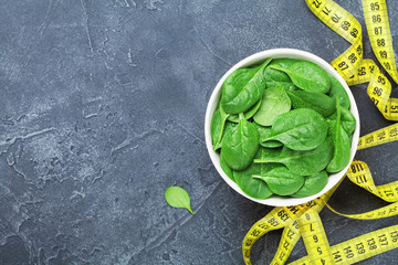 Yellow tape measure and green spinach leaves from above. Diet food concept.