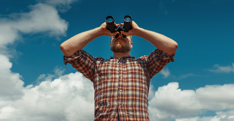 Adventure Search Concept Man Traveler With Berd Looking Through Binoculars In The Distance Against The Sky. Low Angle Point Shoot