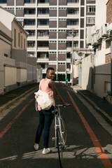 Woman with bicycle in city street