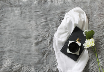 Overheat shot, flower with coffee cup and book.