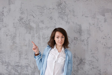 Charming positive girl in casual clothes shows something useful on gray vintage background. Copyspace