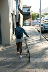 Woman walking with her bicycle on a sidewalk