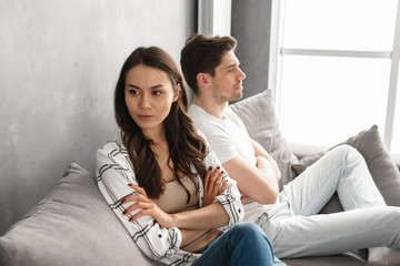Photo of resentful guy and girl acting like arguing couple and not speaking to each other, while sitting together on couch at home, isolated over white background