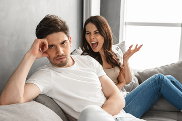 Photo of disappointed couple sitting together on sofa at home with upset look while woman screaming on man, isolated over white background