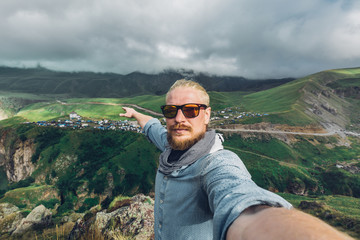 Global Tavel Concept. Young Traveler MAn With A Beard And Sunglasses Take A Selfie On A Background Of A Mountain Landscape