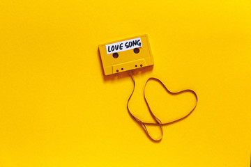 Retro Audio Tape With The Inscription Love Song On A Yellow Background, Top View. Romance Concept