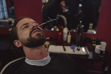 Man getting his beard trimmed with scissors