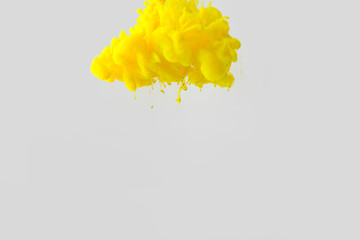 Wall Mural - close up view of bright yellow paint splash in water isolated on gray
