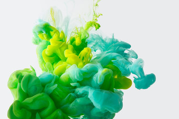 Wall Mural - close up view of mixing of green, yellow and bright turquoise paints splashes in water isolated on gray