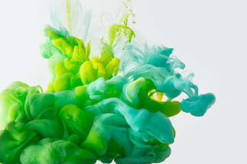 close up view of mixing of green, yellow and bright turquoise paints splashes in water isolated on gray
