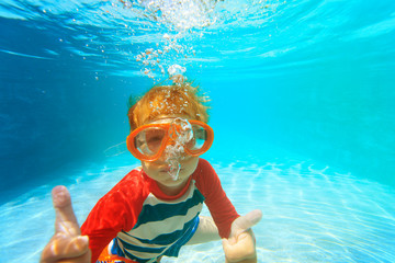 happy little boy swim underwater with thumbs up