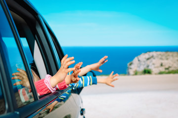 hands of happy kids travel by car on beach