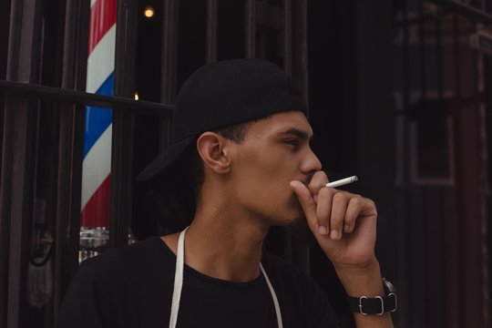Barber smoking cigarette at the entrance of his shop