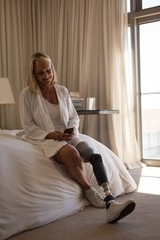 Mature woman with prosthetic leg using mobile phone in bedroom