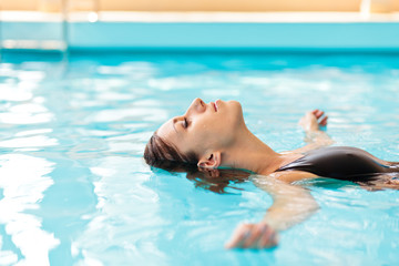 Happy young woman relaxing at swimming pool