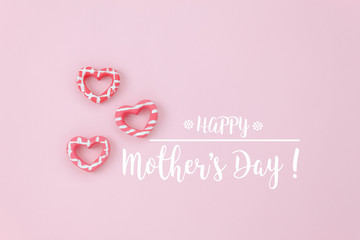 Top view aerial image of decoration Happy mothers day holiday background concept.Flat lay mom text with red heart on modern beautiful  pink paper at home office desk.Free space for creative design.