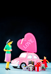 Taiwan, Tainan - April 17, 2018: Miniature people: A mother who is given a heart in love and gifts by little child girl with little bettle pink car, the concept of Mother's Day, blank background for t