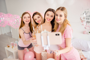 Pretty sexy charming stylish attractive cheerful group of girls enjoying meeting in house, indoor celebrating sleepover holiday event birthday shooting self portrait on front camera using smart phone