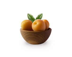 Ripe apricots isolate on a white. Bowl with apricots with leaves isolated on white background. Ripe apricots with copy space for text. Fruit on white background.