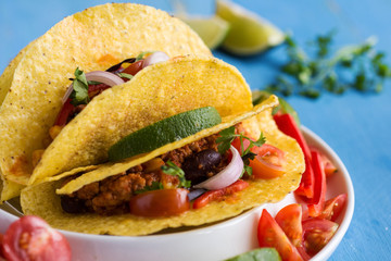 Mexican Tacos with Ground Beef and Vegetables on Rustic Blue Background