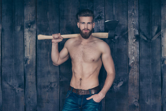 Portrait of attractive sexy strong confident handsome manful brave serious strict brutal unshaven boy with mustache using carrying ax on shoulder isolated on wooden plank background steel