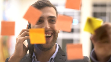 Business man making a mobile meeting with sticky note schedule on window