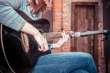 girl playing guitar in recording studio