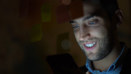Young man using mobile phone at night in dark office