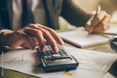 Businessman with calculator counting making notes at office