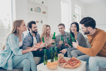 Cheerful, stylish, attractive, positive community sitting in livingroom, house having snacks on the table speaking talking spending free time together enjoying weekend