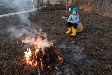 Two happy children in blue work clothes and their young slender mother burn old grass in garden. Family is happy together. Bonfire in front of sunset on a warm spring evening.